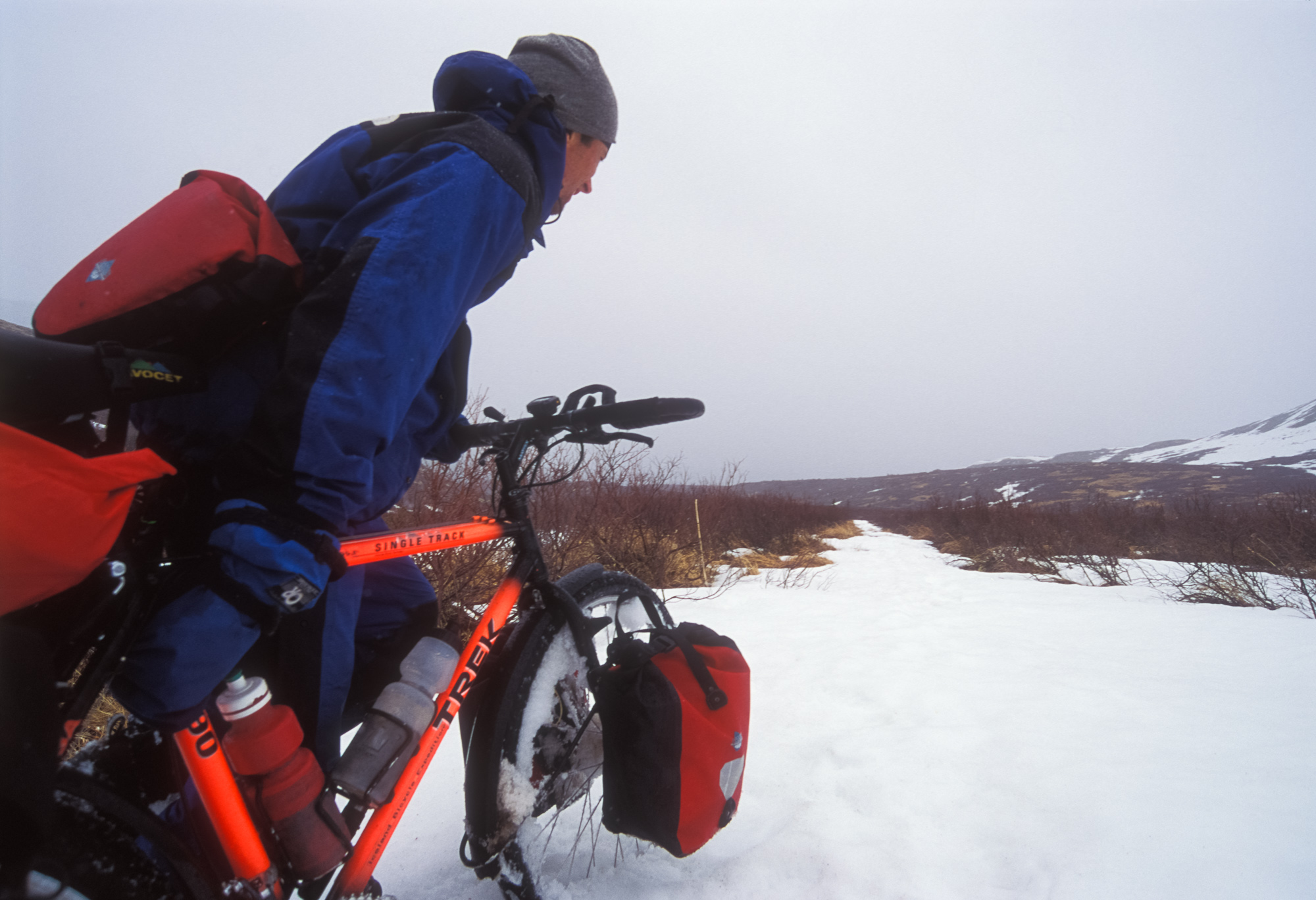 PUSHING THE BIKES UP TO THE PASS WAS MADE MORE DIFFICULT BY WET SNOW COLLECTING IN THE SPOKES.