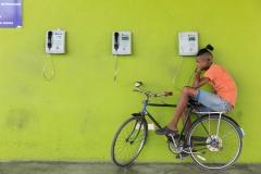 People-Cuban-Man-on-bike-on-phone-bright-wall-john-greengo
